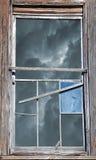Gebroken Venster met Stormachtige Hemel Stock Fotografie