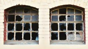 Gebroken vensters van een verlaten, oude fabriek vanuit de tijd van het oprichten royalty-vrije stock afbeeldingen