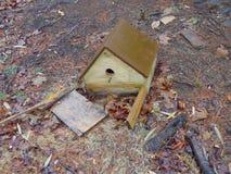 Gebroken Vogelhuis tegen de Dode Bladeren Royalty-vrije Stock Afbeeldingen