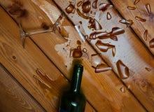 Gebroken wijnglas met fles op lijst royalty-vrije stock foto