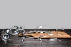 Gebroken wijnglazen en bijl met houten raad Stock Afbeelding
