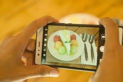 Gebruik een smartphone nemen een beeld van een fruitcake op een achtergrond van de koffiewinkel stock afbeelding