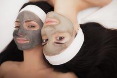 Gebruik van een gezichtsmasker aan gezicht twee jonge vrouwen in een schoonheidssalon Stock Fotografie