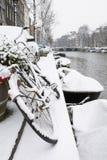 Gebruikelijke fiets in sneeuw dichtbij het kanaal met boten Stock Afbeeldingen