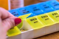 Gebruikend een pillenhouder als dagelijkse herinnering voor het nemen van medicijn Stock Foto
