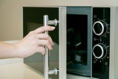 Gebruikend magnetron in de keuken, sluit omhoog foto stock afbeeldingen