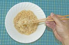 Gebruikseetstokje om Onmiddellijke Noedel te eten stock foto