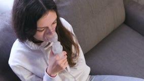 Gebruiksverstuiver en inhaleertoestel voor de behandeling Jonge vrouw die door inhaleertoestelmasker inhaleren stock videobeelden