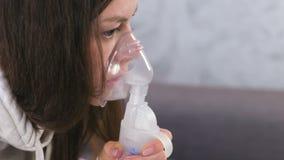 Gebruiksverstuiver en inhaleertoestel voor de behandeling Jonge vrouw die door inhaleertoestelmasker inhaleren Close-upgezicht, z stock video