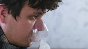 Gebruiksverstuiver en inhaleertoestel voor de behandeling Zieke mens die door inhaleertoestelmasker inhaleren Close-upgezicht, zi stock video