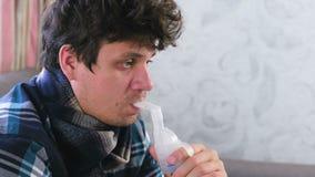 Gebruiksverstuiver en inhaleertoestel voor de behandeling Zieke mens die door inhaleertoestelpijp inhaleren voor keel Het gezicht stock video