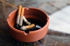 Gebruikt sigaretten en asbakje Royalty-vrije Stock Afbeeldingen