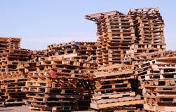 Gebruikte houten pallets die onder open hemel worden gestapeld stock foto's