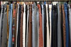 Gebruikte kleding op het rek van de zuinigheidsopslag stock afbeelding