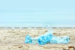Gebruikte plastic flessen op strand, ruimte voor tekst stock foto's