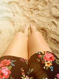 Gebräunte Beine im Sommer sonnen Füße im Sand auf dem Strand Lizenzfreie Stockfotografie