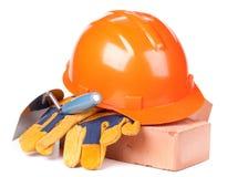 Gebäudeziegelsteine, harter Hut, Trowel und Handschuhe Stockfotografie
