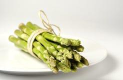Gebundelde groene asperge op een plaat Royalty-vrije Stock Afbeeldingen
