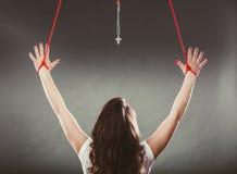 Gebundene Frau gezwungen anzubeten Gefälschte Glaubenreligion stockfotos
