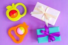 Geburt des Babys - Geschenkbox auf purpurrotem Hintergrund Lizenzfreie Stockfotografie