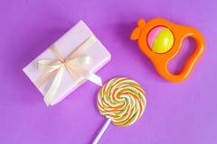 Geburt des Babys - Geschenkbox auf purpurrotem Hintergrund Stockfotos