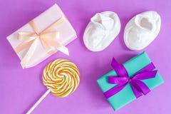 Geburt des Babys - Geschenkbox auf purpurrotem Hintergrund Lizenzfreie Stockbilder