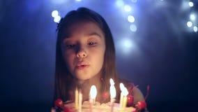 Geburtstag des kleinen Mädchens brennt sie heraus Kerzen auf Kuchen durch Bokeh Hintergrund stock video footage