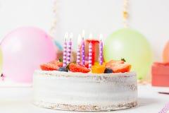 Geburtstag gesunder yougurt Beerenkuchen mit Kerzen auf buntem Parteihintergrund mit hellen Parteiwerkzeugen, Dekoration, gefts u Lizenzfreies Stockbild