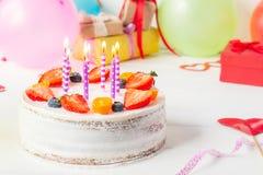 Geburtstag gesunder yougurt Beerenkuchen mit Kerzen auf buntem Parteihintergrund mit hellen Parteiwerkzeugen, Dekoration, gefts u Stockfotografie
