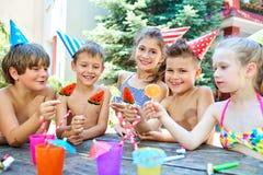 Geburtstag Glückliche Kinder in den Hüten mit Süßigkeit lizenzfreie stockfotografie