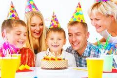 Geburtstag Kleiner Junge brennt heraus Kerzen auf Geburtstagskuchen durch Lizenzfreies Stockbild