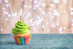 Geburtstagkleiner kuchen mit brennender Kerze Stockfotografie