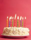 Geburtstagkuchen auf rotem Hintergrund Lizenzfreie Stockbilder