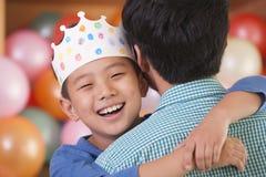 Geburtstags-Junge, der seinen Vater umarmt Lizenzfreies Stockbild