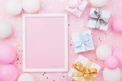 Geburtstags- oder Feiertagsmodell mit Rahmen, Geschenkbox, Pastellballonen und Konfettis auf rosa Tischplatteansicht Flache Lagez Lizenzfreies Stockfoto