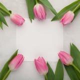 Geburtstags- oder Hochzeitsmodell mit Weißbuchliste, rosa Tulpe blüht auf Draufsicht des blauen Hintergrundes Schönheitstageskart Stockfotografie