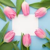Geburtstags- oder Hochzeitsmodell mit Weißbuchliste, rosa Tulpe blüht auf Draufsicht des blauen Hintergrundes Schönheitstageskart Lizenzfreie Stockfotos