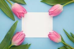 Geburtstags- oder Hochzeitsmodell mit Weißbuchliste, rosa Tulpe blüht auf Draufsicht des blauen Hintergrundes Schönheitstageskart Lizenzfreie Stockbilder