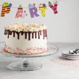 Geburtstags-Tropfenfänger-überlagerter Kuchen mit Schokolade ganache und besprüht auf einem weißen Hintergrund mit Parteidekor ho lizenzfreie stockfotos