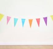 Geburtstagsdekorationsflaggen auf einer einfachen weißen Wand Stockfotografie