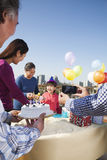 Geburtstagsfeier, Familie von mehreren Generationen, den Kuchen zum Tabelle holend Lizenzfreie Stockfotografie