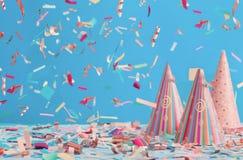 Geburtstagshut und -Konfettis auf blauem Hintergrund Lizenzfreie Stockfotografie