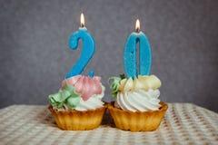 Geburtstagsjahrestag 20 Jahre mit Kuchen und blauen Kerzen Lizenzfreies Stockfoto