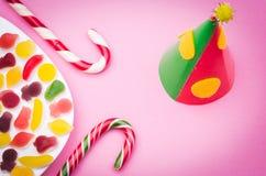 Geburtstagskappe und -süßigkeit auf einem hellvioletten Hintergrund Lizenzfreie Stockfotos