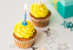 Geburtstagskleine kuchen mit brennenden Kerzen Lizenzfreie Stockfotos