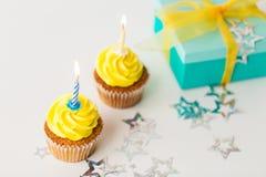 Geburtstagskleine kuchen mit brennenden Kerzen und Geschenk Lizenzfreies Stockbild