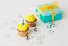Geburtstagskleine kuchen mit brennenden Kerzen und Geschenk Lizenzfreie Stockfotografie