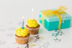 Geburtstagskleine kuchen mit brennenden Kerzen und Geschenk Stockfoto