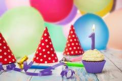 Geburtstagskleiner kuchen, Ausblasen und Parteihüte lizenzfreies stockfoto
