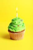 Geburtstagskleiner kuchen mit Buttercreme und Kerze auf gelbem Hintergrund Lizenzfreie Stockfotografie